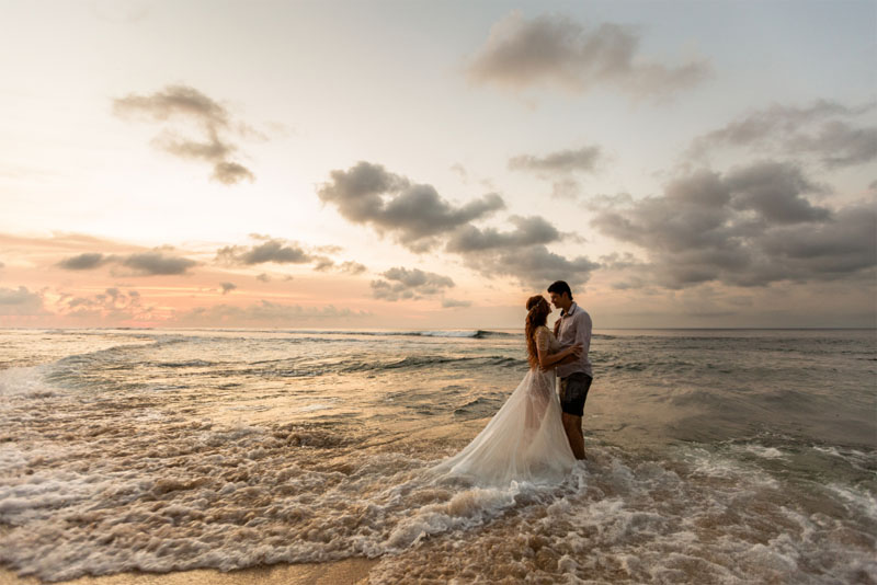 photo of a couple on the beach in wedding clothes